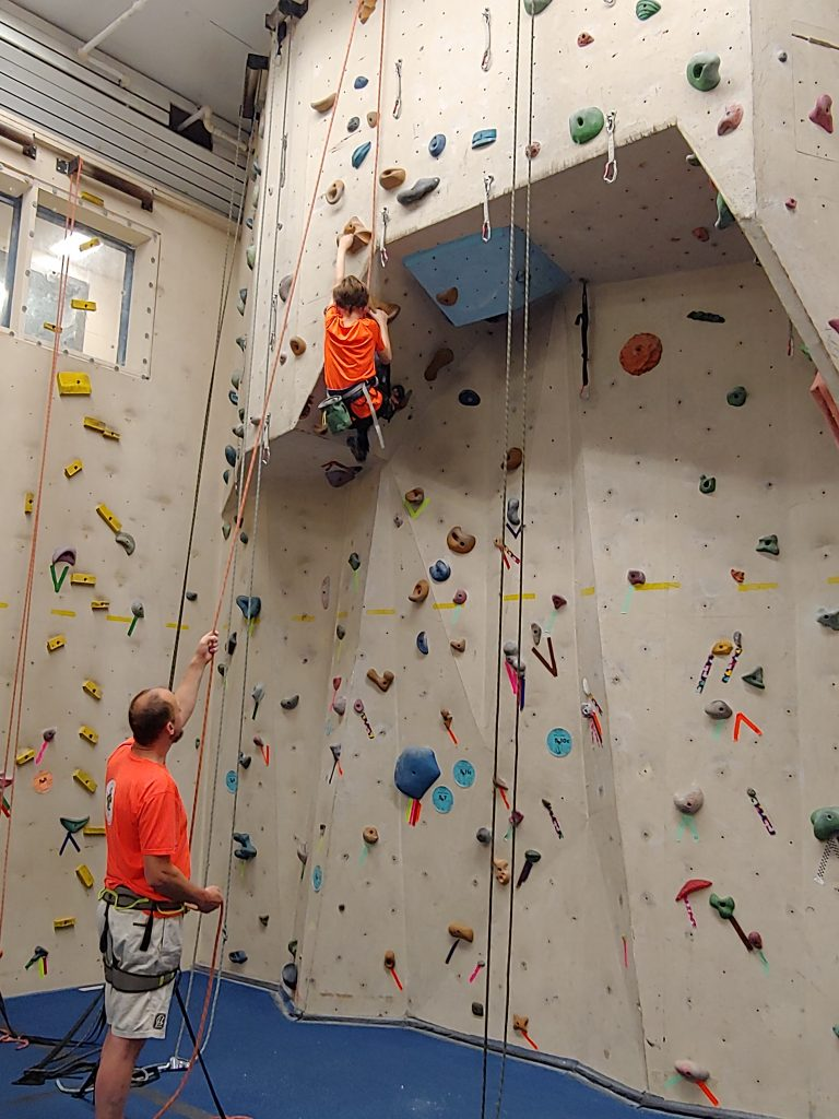 Family Climb activity with father and son. The dad is belaying for his kid that is climbing.