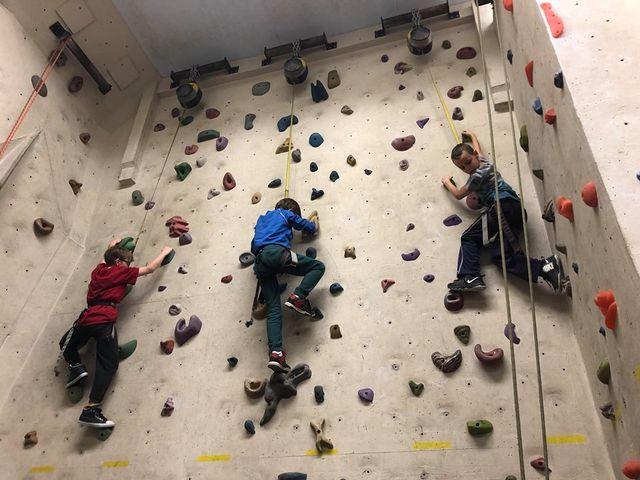 Three kids climbing a wall in the Ajax Rock Oasis Climbing Camp