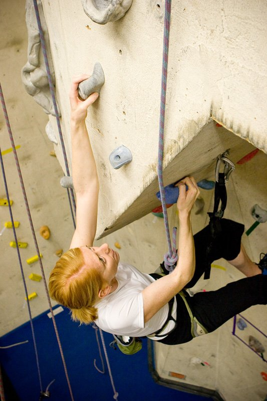 Blonde woman climbing at Ajax Rock Oasis Indoor Gym - Hours of Operation